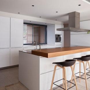 Diseño de cocina en L, contemporánea, con armarios con paneles lisos, puertas de armario blancas, electrodomésticos de acero inoxidable, una isla y suelo gris