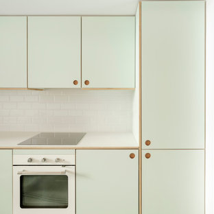 Design ideas for a small scandinavian single-wall open plan kitchen in Madrid with a drop-in sink, shaker cabinets, green cabinets, laminate benchtops, white splashback, ceramic splashback, stainless steel appliances, concrete floors, no island, grey floor and green benchtop.