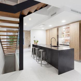 Imagen de cocina lineal, minimalista, con armarios con paneles lisos, una isla, encimeras negras, fregadero de un seno, puertas de armario de madera clara y suelo blanco