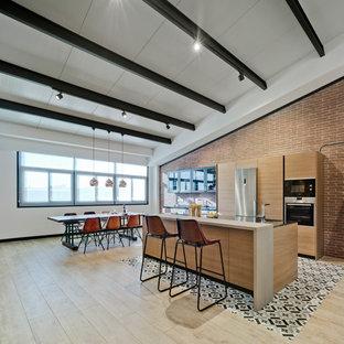 Foto de cocina comedor lineal, actual, grande, con armarios con paneles lisos, puertas de armario de madera oscura, suelo de madera clara, una isla, electrodomésticos de acero inoxidable y suelo beige