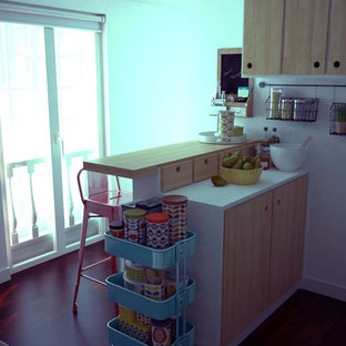 他の地域の小さいミッドセンチュリースタイルのおしゃれなキッチン (ドロップインシンク、フラットパネル扉のキャビネット、淡色木目調キャビネット、タイルカウンター、白い調理設備、濃色無垢フローリング、アイランドなし、白いキッチンカウンター) の写真