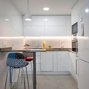 Foto de cocina comedor en L, actual, con fregadero bajoencimera, armarios con paneles lisos, puertas de armario blancas, salpicadero blanco, electrodomésticos blancos y suelo beige