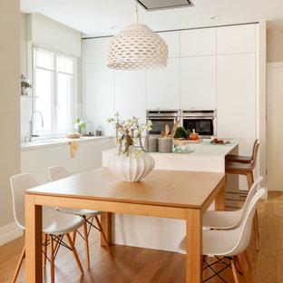 Foto de cocina comedor en L, contemporánea, de tamaño medio, con armarios con paneles lisos, puertas de armario blancas, electrodomésticos de acero inoxidable, una isla, suelo marrón, salpicadero blanco y suelo de madera en tonos medios