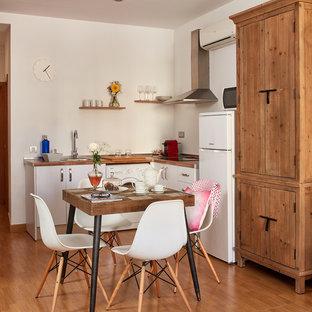 Ejemplo de cocina comedor en L, campestre, pequeña, sin isla, con armarios con paneles lisos, puertas de armario blancas, encimera de madera, salpicadero blanco, electrodomésticos blancos y suelo de madera en tonos medios