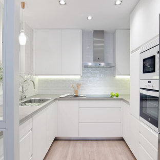 This is an example of a mid-sized contemporary u-shaped separate kitchen in Madrid with a single-bowl sink, white cabinets, concrete benchtops, white splashback, ceramic splashback, white appliances, light hardwood floors, no island, flat-panel cabinets and beige floor.