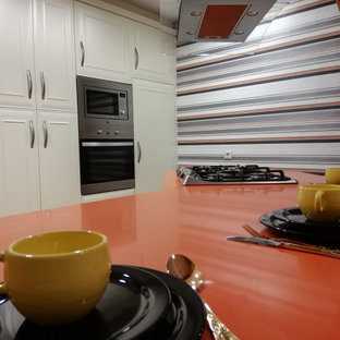 This is an example of a small traditional u-shaped eat-in kitchen in Malaga with an undermount sink, beaded inset cabinets, white cabinets, quartz benchtops, stainless steel appliances, terrazzo floors, a peninsula, multi-coloured floor and orange benchtop.