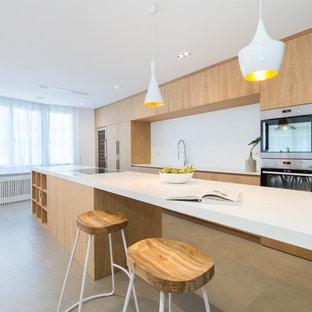 Imagen de cocina de galera, actual, con fregadero integrado, armarios con paneles lisos, puertas de armario de madera clara, salpicadero blanco, electrodomésticos de acero inoxidable, una isla, suelo gris y encimeras blancas