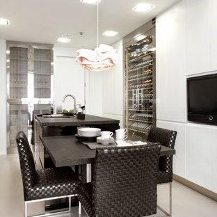 Modelo de cocina en U, contemporánea, grande, con fregadero bajoencimera, armarios con paneles lisos, puertas de armario blancas, electrodomésticos con paneles, una isla, suelo gris y encimeras negras