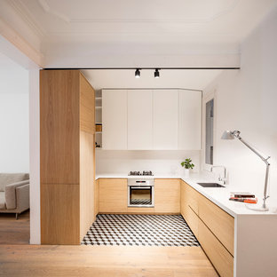 Photo of a mid-sized scandinavian u-shaped open plan kitchen in Barcelona with flat-panel cabinets, white splashback, stainless steel appliances, ceramic floors, no island, multi-coloured floor, a single-bowl sink, light wood cabinets and quartz benchtops.
