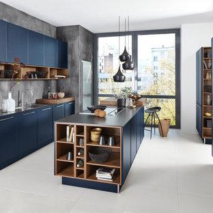 Foto de cocina contemporánea con armarios con paneles lisos, puertas de armario azules, una isla, fregadero de doble seno, salpicadero verde y suelo blanco