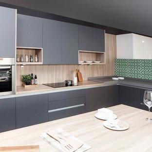 マドリードの大きいモダンスタイルのおしゃれなキッチン (エプロンフロントシンク、フラットパネル扉のキャビネット、グレーのキャビネット、木材カウンター、木材のキッチンパネル、シルバーの調理設備、グレーのキッチンカウンター) の写真
