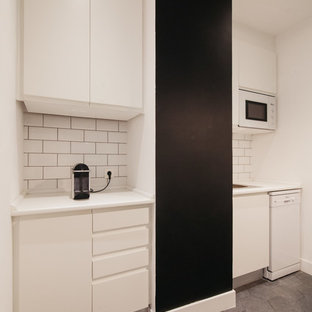 マドリードの中サイズのインダストリアルスタイルのおしゃれなキッチン (シングルシンク、フラットパネル扉のキャビネット、白いキャビネット、白いキッチンパネル、セラミックタイルのキッチンパネル、白い調理設備、アイランドなし) の写真