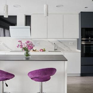 Modelo de cocina en U, contemporánea, de tamaño medio, con fregadero bajoencimera, armarios con paneles lisos, puertas de armario blancas, salpicadero verde, electrodomésticos con paneles, península, suelo gris y encimeras grises