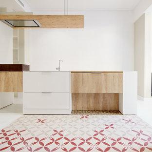 Diseño de cocina lineal, mediterránea, de tamaño medio, abierta, con armarios con paneles lisos, puertas de armario de madera clara, encimera de cuarcita y una isla