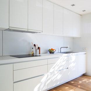 Diseño de cocina lineal, minimalista, de tamaño medio, abierta, sin isla, con armarios con paneles lisos, puertas de armario blancas, salpicadero blanco, suelo de madera en tonos medios, electrodomésticos de acero inoxidable, fregadero de un seno, encimera de laminado y suelo marrón
