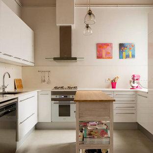 Imagen de cocina en U, urbana, de tamaño medio, cerrada, con puertas de armario blancas, suelo de cemento, una isla, suelo gris, salpicadero blanco, fregadero bajoencimera, armarios con paneles lisos y electrodomésticos de acero inoxidable