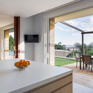 Diseño de cocina contemporánea, de tamaño medio, abierta, con armarios con paneles lisos, puertas de armario de madera clara y una isla