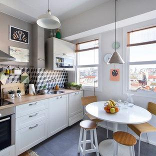 マドリードの中サイズのエクレクティックスタイルのおしゃれなキッチン (シングルシンク、落し込みパネル扉のキャビネット、白いキャビネット、木材カウンター、マルチカラーのキッチンパネル、セラミックタイルのキッチンパネル、シルバーの調理設備の、セラミックタイルの床、アイランドなし、黒い床) の写真