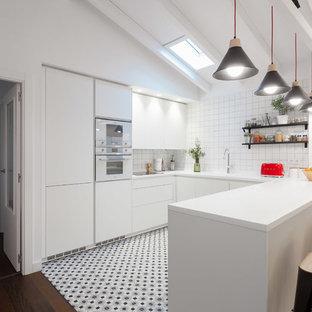Imagen de cocina en U, contemporánea, con armarios con paneles lisos, puertas de armario blancas, salpicadero blanco, electrodomésticos blancos, península, encimeras blancas y suelo gris