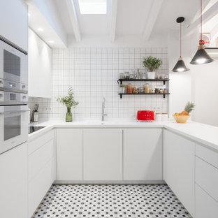 Diseño de cocina en U, actual, con fregadero integrado, armarios con paneles lisos, puertas de armario blancas, salpicadero blanco, electrodomésticos blancos, península, suelo multicolor y encimeras blancas