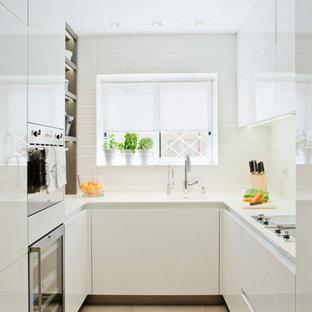 Modelo de cocina en U, tradicional renovada, pequeña, cerrada, sin isla, con armarios con paneles lisos, puertas de armario blancas y salpicadero blanco