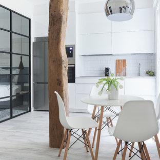 マドリードの小さい北欧スタイルのおしゃれなキッチン (フラットパネル扉のキャビネット、白いキャビネット、白いキッチンパネル、サブウェイタイルのキッチンパネル、アイランドなし、アンダーカウンターシンク、シルバーの調理設備、ラミネートの床、グレーの床、白いキッチンカウンター) の写真
