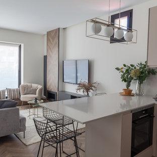 マドリードの中くらいの北欧スタイルのおしゃれなキッチン (アンダーカウンターシンク、フラットパネル扉のキャビネット、ベージュのキャビネット、クオーツストーンカウンター、ベージュキッチンパネル、ライムストーンのキッチンパネル、黒い調理設備、ラミネートの床、茶色い床、ベージュのキッチンカウンター) の写真