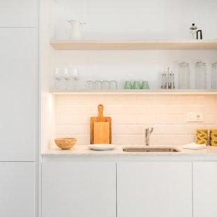 Diseño de cocina lineal, contemporánea, pequeña, con fregadero bajoencimera, armarios con paneles lisos, puertas de armario blancas, encimera de mármol, salpicadero blanco, salpicadero de azulejos tipo metro y electrodomésticos con paneles