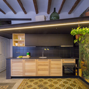 Photo of a mid-sized tropical single-wall eat-in kitchen in Barcelona with flat-panel cabinets, black cabinets, ceramic floors, no island and multi-coloured floor.