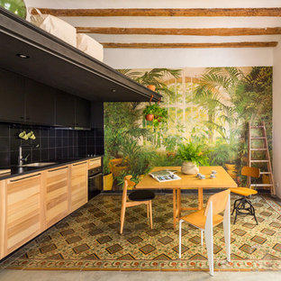 Photo of a mid-sized tropical single-wall eat-in kitchen in Barcelona with an undermount sink, medium wood cabinets, black splashback, ceramic splashback, black appliances, ceramic floors, no island, multi-coloured floor and flat-panel cabinets.