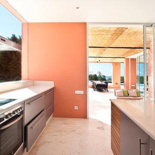Ejemplo de cocina mediterránea con armarios con paneles lisos, puertas de armario grises, electrodomésticos de acero inoxidable, una isla, suelo blanco, salpicadero verde y encimeras grises