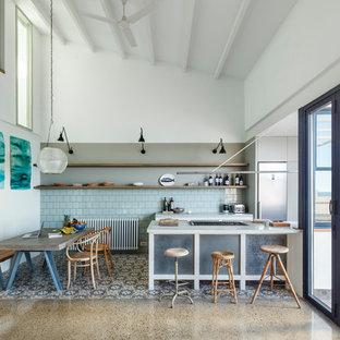 Foto de cocina lineal, mediterránea, de tamaño medio, abierta, con puertas de armario grises, salpicadero azul y península