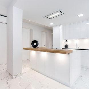 Imagen de cocina contemporánea con armarios con paneles lisos, puertas de armario blancas, salpicadero blanco, electrodomésticos negros, una isla, suelo blanco y encimeras blancas