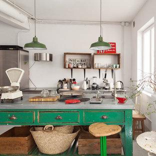 マドリードのエクレクティックスタイルのおしゃれなキッチン (ドロップインシンク、フラットパネル扉のキャビネット、緑のキャビネット、白いキッチンパネル、シルバーの調理設備の、グレーの床、グレーのキッチンカウンター) の写真