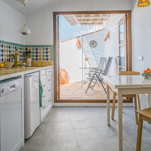 Ispirazione per una cucina lineare mediterranea chiusa e di medie dimensioni con ante lisce, ante bianche, top piastrellato, paraspruzzi multicolore, paraspruzzi con piastrelle in ceramica, pavimento con piastrelle in ceramica e nessuna isola