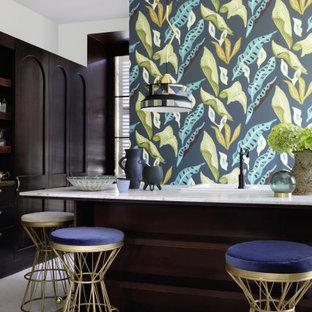 Ejemplo de cocina en L, tradicional renovada, grande, con fregadero encastrado, puertas de armario de madera en tonos medios, península, suelo gris, encimeras blancas y papel pintado