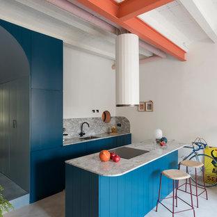 Foto de cocina de galera, industrial, con armarios con paneles con relieve, puertas de armario turquesas, salpicadero verde, electrodomésticos con paneles, una isla, suelo gris y encimeras grises