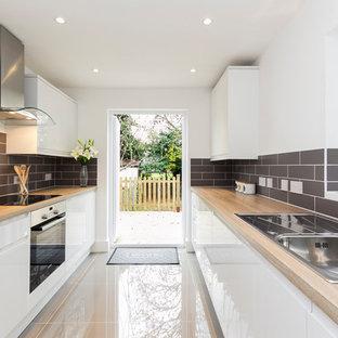 Modelo de cocina lineal, actual, con fregadero sobremueble, armarios con paneles lisos, puertas de armario blancas, encimera de madera, salpicadero verde y electrodomésticos de acero inoxidable