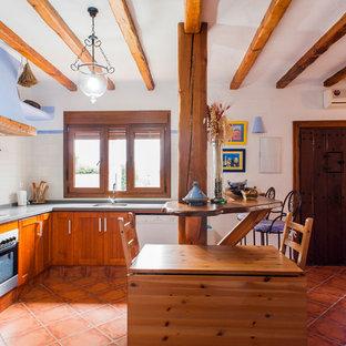 Ejemplo de cocina en L, mediterránea, con armarios con paneles empotrados, puertas de armario de madera oscura, salpicadero blanco, electrodomésticos blancos, península, suelo rojo y encimeras grises