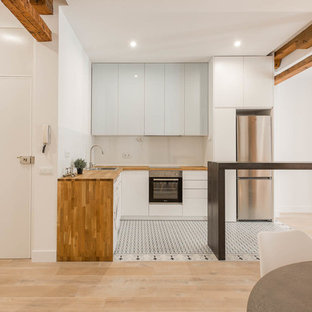 Mid-sized scandinavian open concept kitchen designs - Inspiration for a mid-sized scandinavian l-shaped ceramic floor and multicolored floor open concept kitchen remodel in Madrid with flat-panel cabinets, wood countertops, white backsplash, glass sheet backsplash, stainless steel appliances, a peninsula, a drop-in sink and blue cabinets