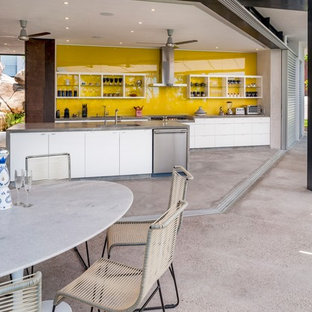 Large contemporary single-wall open plan kitchen in Mexico City with a single-bowl sink, open cabinets, white cabinets, concrete benchtops, yellow splashback, glass tile splashback, stainless steel appliances, concrete floors, with island and grey floor.