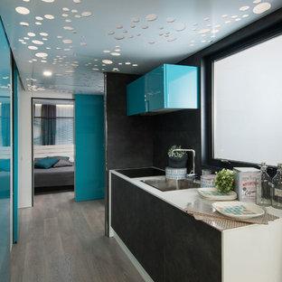 Diseño de cocina de galera, contemporánea, con fregadero encastrado, armarios con paneles lisos, puertas de armario negras, salpicadero negro, suelo de madera clara, suelo beige y encimeras blancas