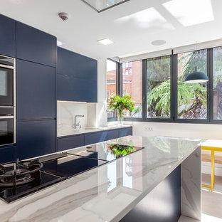 Diseño de cocina comedor contemporánea con fregadero bajoencimera, armarios con paneles lisos, puertas de armario azules, encimera de mármol, salpicadero blanco, salpicadero de mármol, electrodomésticos negros, una isla, suelo beige y encimeras blancas