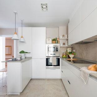 Foto de cocina en U, minimalista, de tamaño medio, abierta, con armarios con paneles lisos, puertas de armario blancas, electrodomésticos de acero inoxidable, península, suelo beige y encimeras grises