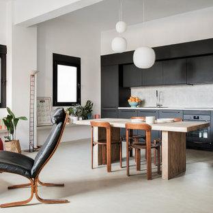 Ejemplo de cocina lineal, escandinava, abierta, con armarios con paneles lisos, puertas de armario negras, salpicadero verde, electrodomésticos negros, suelo de cemento, suelo gris y encimeras grises
