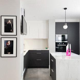 Diseño de cocina en L, actual, de tamaño medio, abierta, con fregadero bajoencimera, armarios con paneles lisos, puertas de armario grises, encimera de mármol, salpicadero blanco, suelo de cemento, una isla, suelo gris y electrodomésticos negros