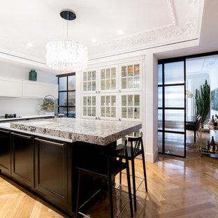 Imagen de cocina actual, cerrada, con fregadero bajoencimera, armarios con paneles empotrados, puertas de armario negras, salpicadero blanco, una isla, encimeras blancas y suelo de madera clara