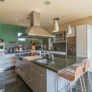 Modelo de cocina en L, actual, con fregadero bajoencimera, armarios con paneles lisos, puertas de armario grises, electrodomésticos de acero inoxidable, una isla, suelo verde y encimeras verdes