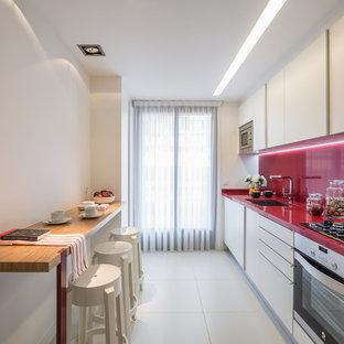 Пример оригинального дизайна: линейная кухня среднего размера в стиле модернизм с обеденным столом, одинарной раковиной, плоскими фасадами, белыми фасадами, красным фартуком, техникой из нержавеющей стали, полом из керамической плитки и красной столешницей без острова