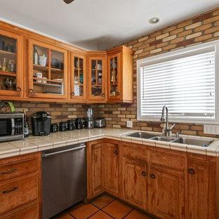 ロサンゼルスのトラディショナルスタイルのおしゃれなキッチン (トリプルシンク、シェーカースタイル扉のキャビネット、ヴィンテージ仕上げキャビネット、タイルカウンター、マルチカラーのキッチンパネル、レンガのキッチンパネル、シルバーの調理設備の、テラコッタタイルの床、アイランドなし、オレンジの床、ベージュのキッチンカウンター) の写真